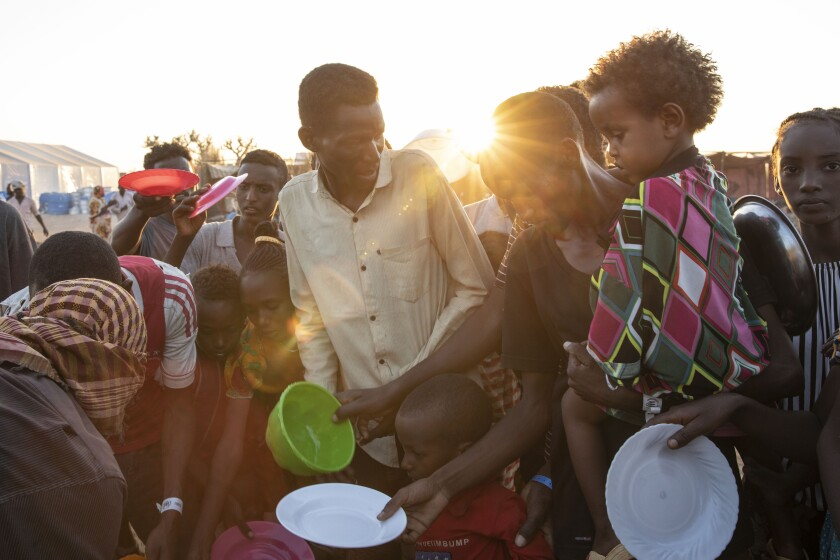 Refugees from the conflict in Ethiopia's Tigray region wait for food served by volunteers in eastern Sudan on Monday.