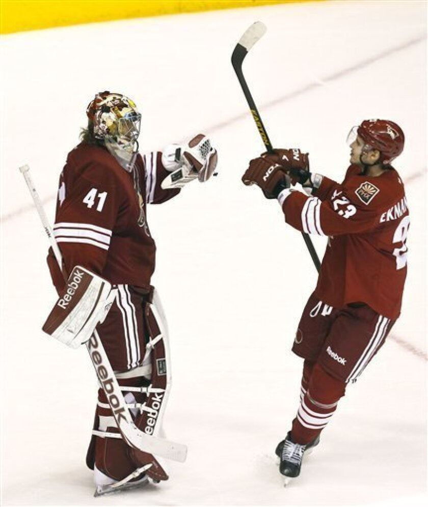 Phoenix Coyotes' Mike Smith (41) celebrates a win with teammate Oliver Ekman-Larsson (23), of Sweden, at the end of an NHL hockey game against the Dallas Stars, Saturday, March 9, 2013, in Glendale, Ariz. The Coyotes defeated the Stars 2-1. (AP Photo/Ross D. Franklin)