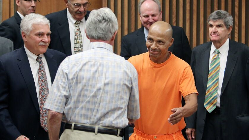Louis Taylor shakes the hand of his first attorney from 1972, Howard Kashman, as his current defense team from Phoenix surrounds him after a hearing in Pima County Superior Court in Tucson in 2013.