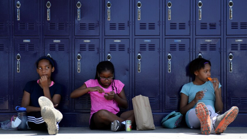 Marley Streeck, 11, from left, Lauren D. Wright, 10, and Grace Ajegbo, 11, sit together during their lunch break at the Girls Academic Leadership Academy (GALA) orientation in Los Angeles.