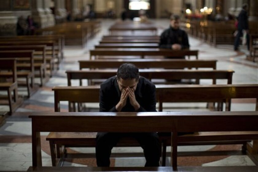 """A priest prays inside the Church of Saint Ignatius, dedicated to Ignatius of Loyola, the founder of the Jesuit order, in Rome, Thursday, March 14, 2013. Pope have punished Jesuits theologians for being too progressive in preaching and teaching. The last pontiff, Benedict, politely but firmly sent a letter to the Jesuit's leader inviting members to pledge """"total adhesion"""" to Catholic doctrine, including on divorce, homosexuality and liberation theology. Now the pope is a Jesuit, the first ever fr"""