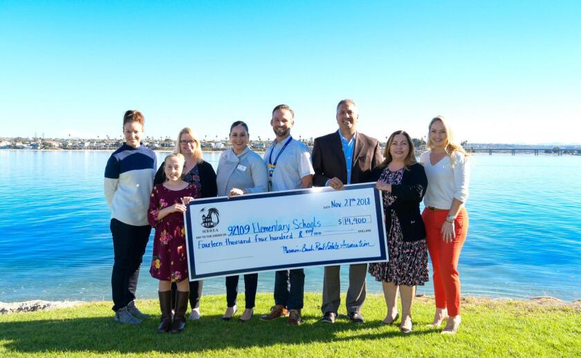 Posing with a $14,400 donation from MBREA are volunteers and elementary school principals.