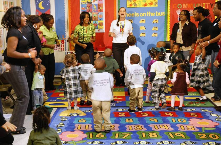 """First Lady Michelle Obama exercises with staff, parents and children at the Royal Castle Child Development Center in New Orleans in 2011 as part of her """"Let's Move!"""" campaign."""
