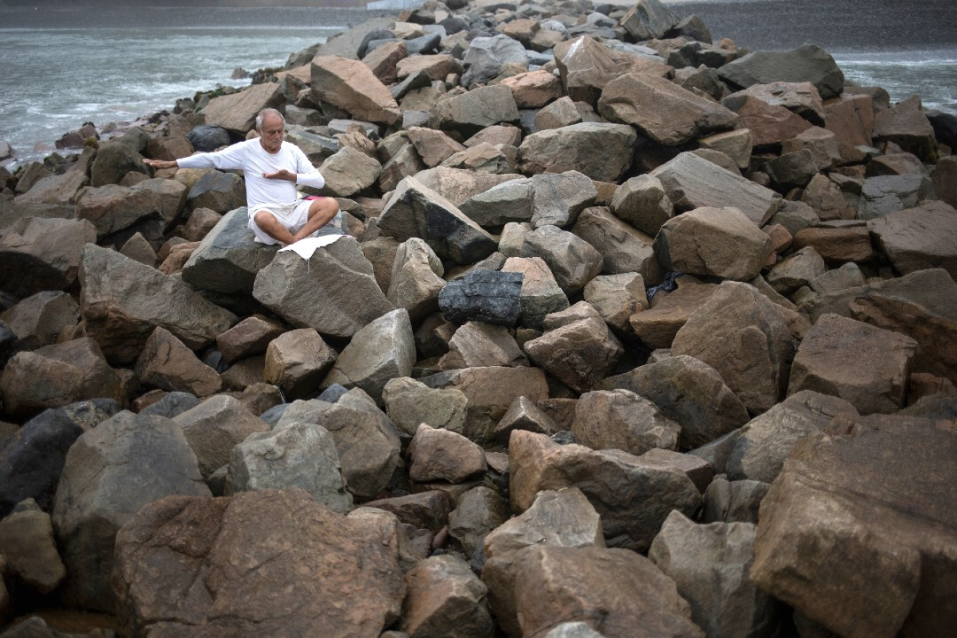 Tomas Cabrera, 86, meditates on a jetty at Agua Dulce beach on March 25, in defiance of government orders to stay away.