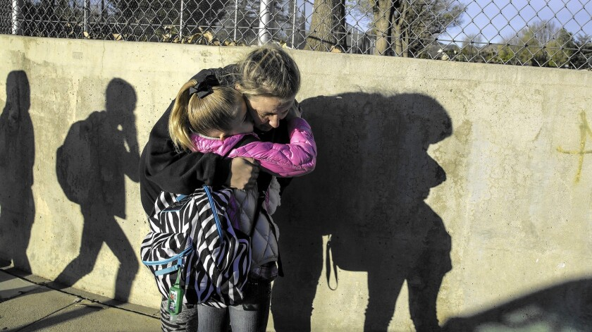 Leah Hooper, 8, hugs her mother, Tiffany, as she is dropped off at Germain Street Elementary School.