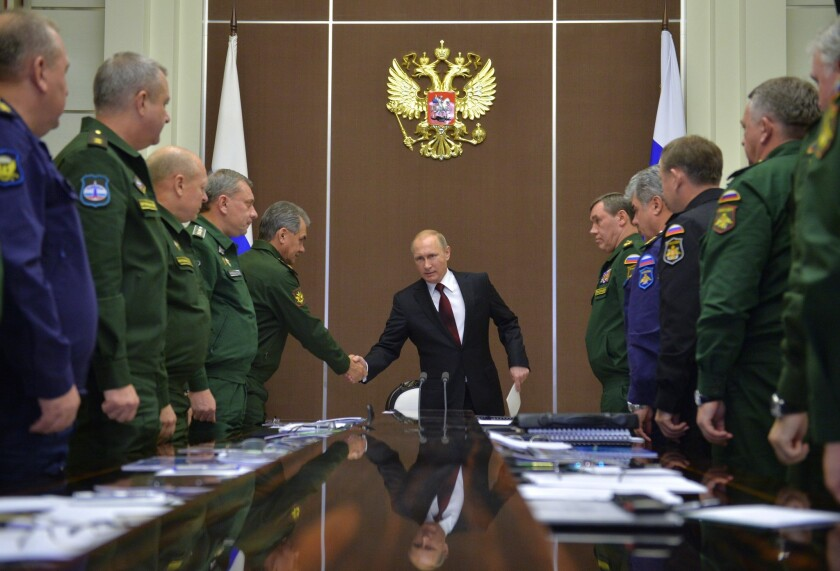 Russian President Vladimir Putin, center, shakes hands with Defense Minister Sergei Shoigu at a meeting with top military officials in Sochi, Russia, on Nov. 24.