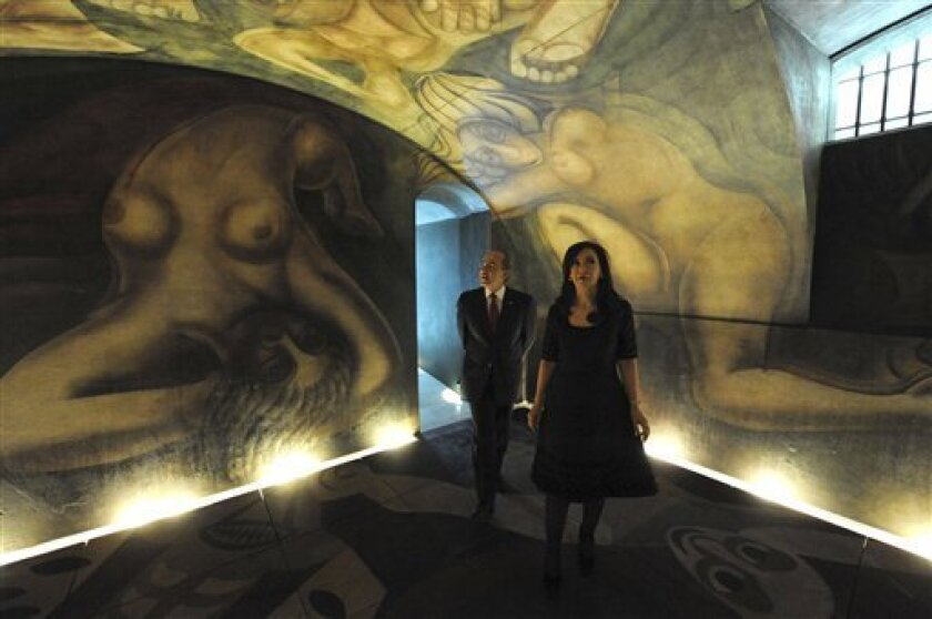 """In this picture released by Argentina's Presidential Press Office, Argentina's President Cristina Fernandez, right, accompanied by Mexican President Felipe Calderon walk along the mural entitled """"Ejercicio Plastico"""" by Mexican artist David Siqueiros after its inauguration, in Buenos Aires, Argentina, Friday, Dec. 3, 2010. The mural which spent years under restoration, has been placed at the future Museum of Political Arts, a former underground customs facility, next to the government house. (AP Photo/Argentine Presidential Press Office)"""