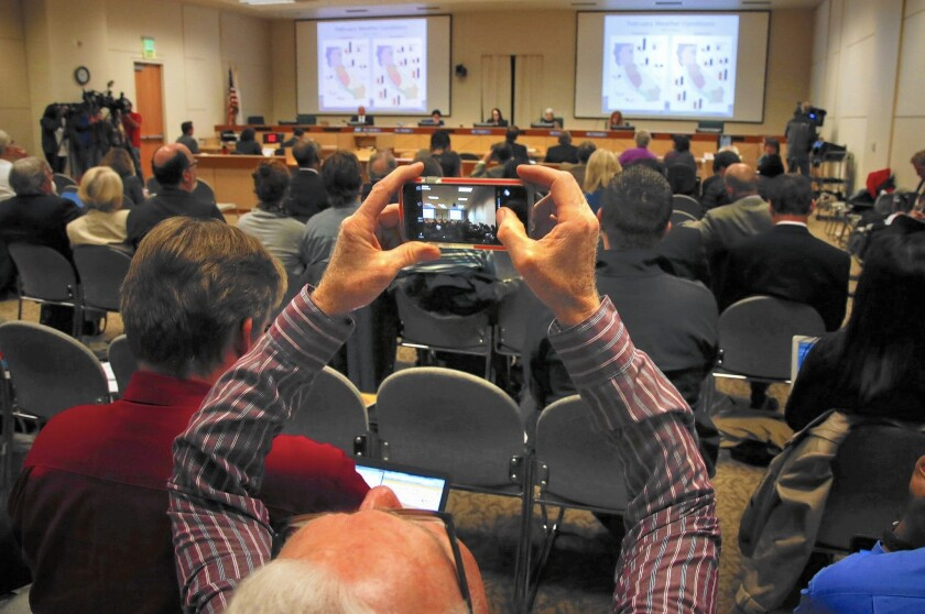 Audience members snap photos of the grim conservation statistics flashing on the screen at a State Water Resources Control Board meeting in Sacramento.