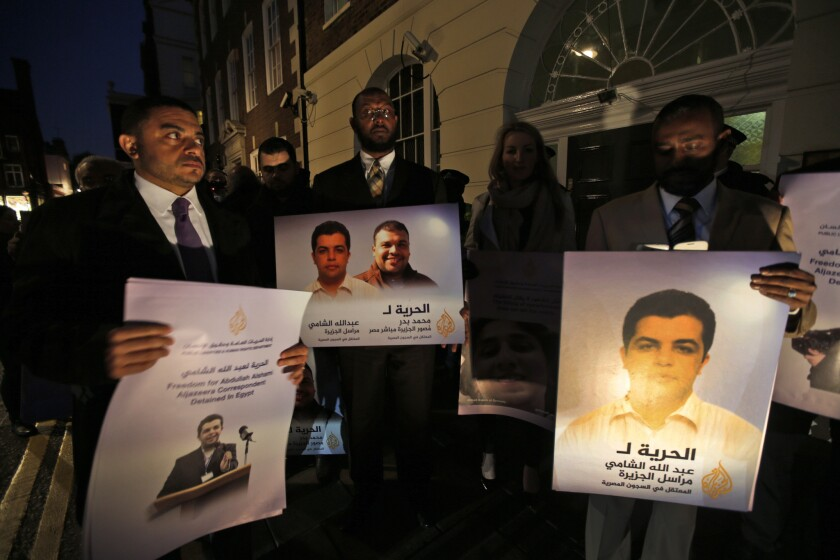 Demonstrators outside the Egyptian Embassy in London hold placards with pictures of Al Jazeera journalists being held by Egyptian authorities.