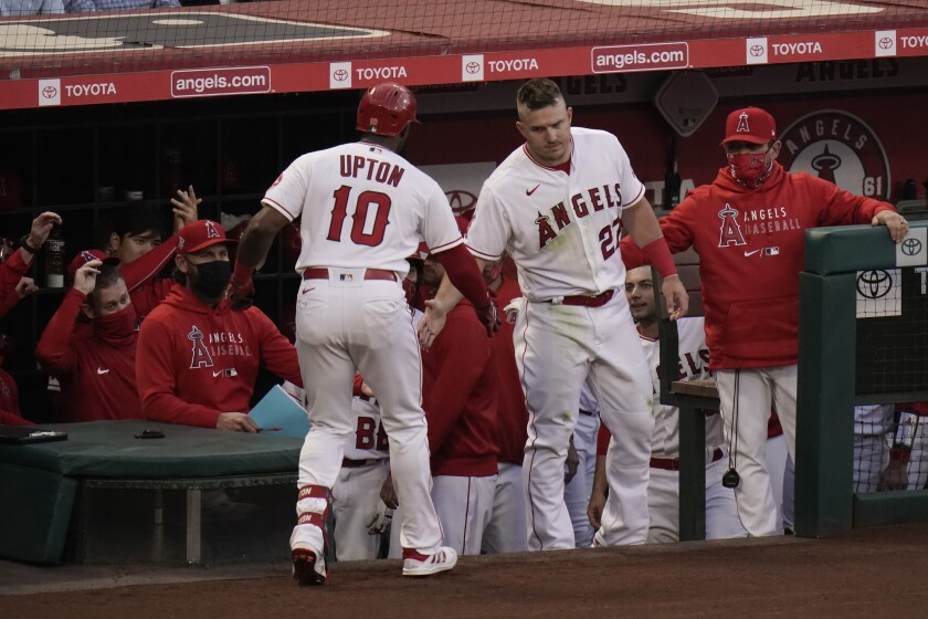 Los Angeles Angels' Justin Upton, left, is congratulated by Mike Trout after hitting a home run during the second inning of a baseball game against the Los Angeles Dodgers, Friday, May 7, 2021, in Anaheim, Calif. (AP Photo/Jae C. Hong)