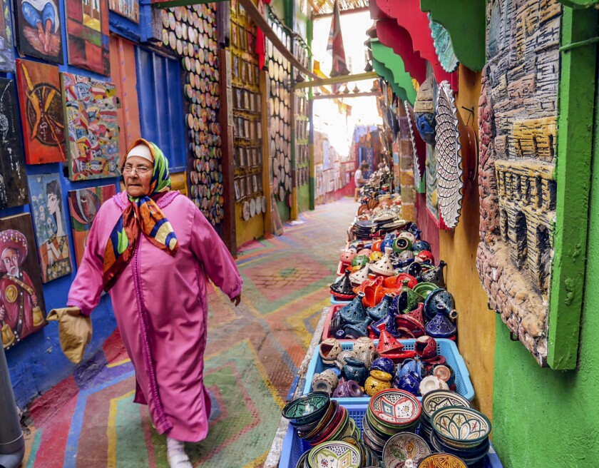 FEZ, MOROCCO - A woman walks down a gaily painted alley in the ancient walled city in Fez.