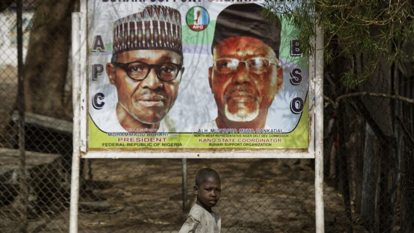 A boy scavenges for items to sell as he walks past a campaign sign for incumbent President Muhammadu Buhari, left, and local party official Mustapha Dankadai in Kano, northern Nigeria.