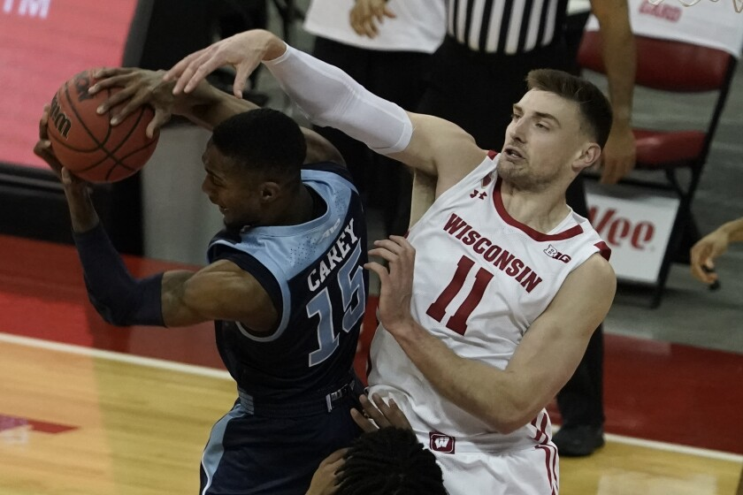 Rhode Island's Jalen Carey and Wisconsin's Micah Potter battle for a rebound during the second half of an NCAA college basketball game Wednesday, Dec. 9, 2020, in Madison, Wis. (AP Photo/Morry Gash)