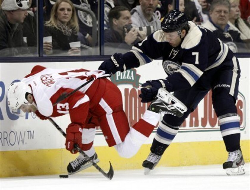 Columbus Blue Jackets' Jack Johnson, right, checks Detroit Red Wings' Pavel Datsyuk, of Russia, in the second period of an NHL hockey game in Columbus, Ohio, Saturday, Feb. 2, 2013. (AP Photo/Paul Vernon)