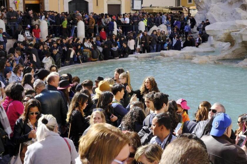 Un grupo de turistas visita la Fontana Di Trevi, durante la tarde de Pascua, en Roma. EFE/Archivo