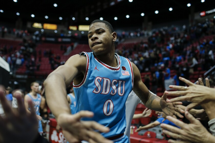 SDSU forward Keshad Johnson (0) high fives fans after the Aztecs victory over Tennessee State.
