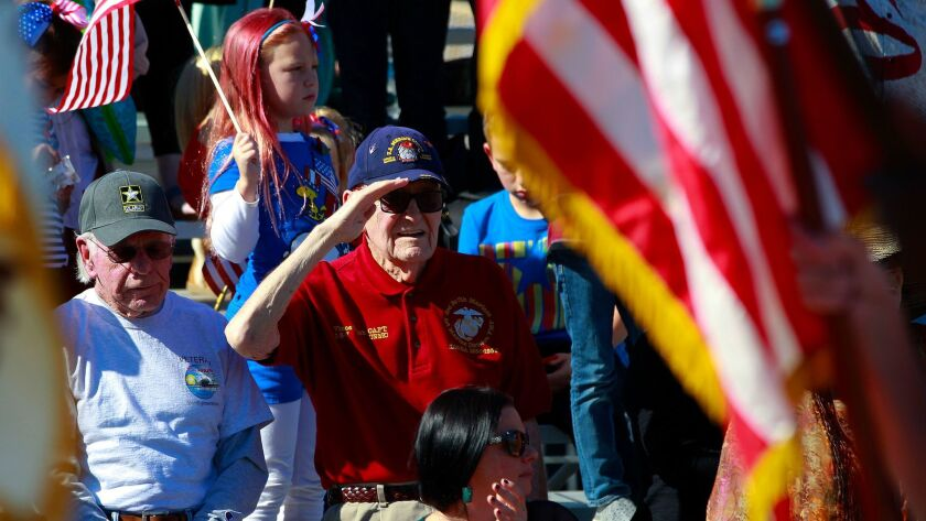 Vincent Walsh a U.S. Marine veteran who served in WWII and the Korean War stood up and saluted for each color guard unit that marched in the San Diego Veterans Day Parade on Nov. 11, 2015.
