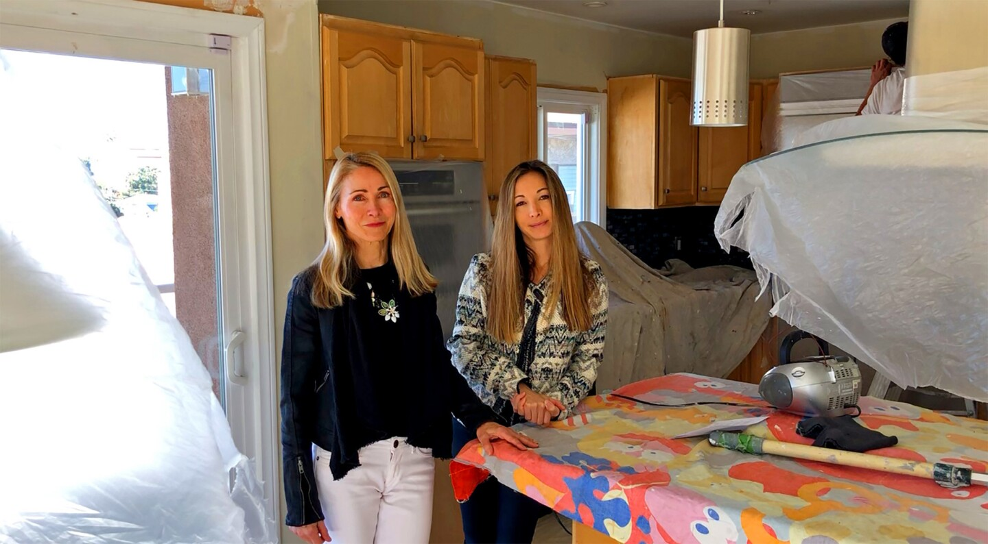 Real estate agents Cari Corbalis, left, and daughter Britt stand in the kitchen of one of their listings prior to painting.