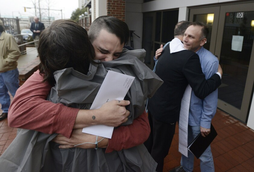 Justin Morgan, left, and Glenn Cannon, right, hug supporters after getting their marriage license in Montgomery, Ala.