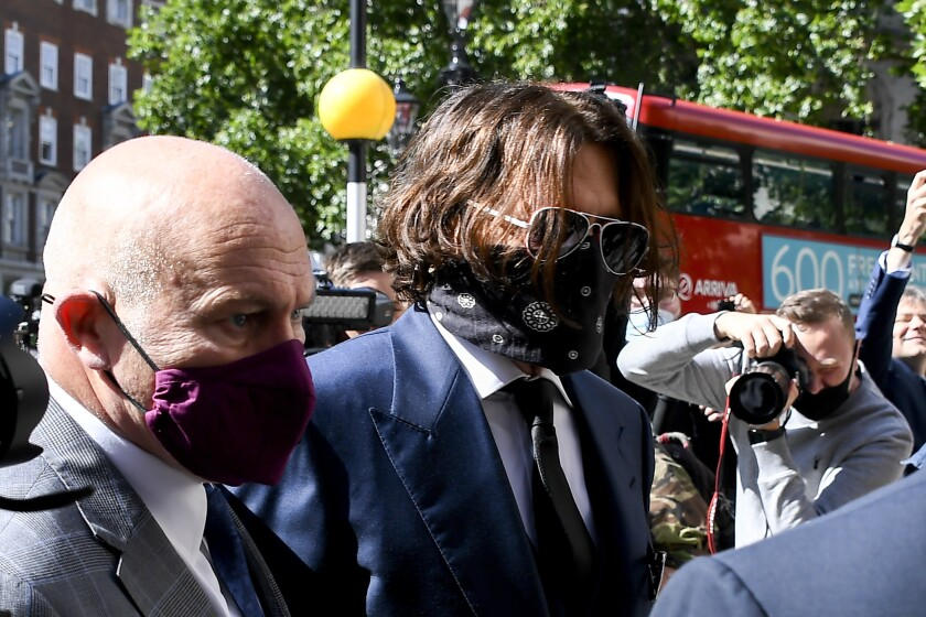 Johnny Depp wears sunglasses and a face covering as he walks through a crowd.
