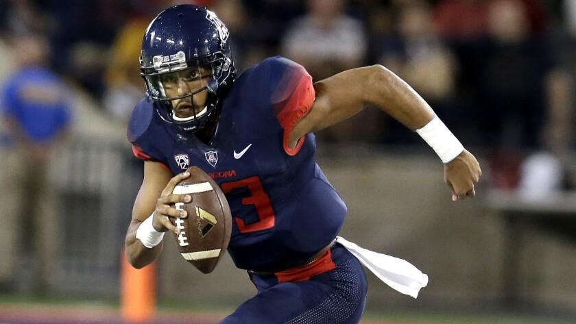 Arizona quarterback Brandon Dawkins scrambles for a gain against Washington last week.