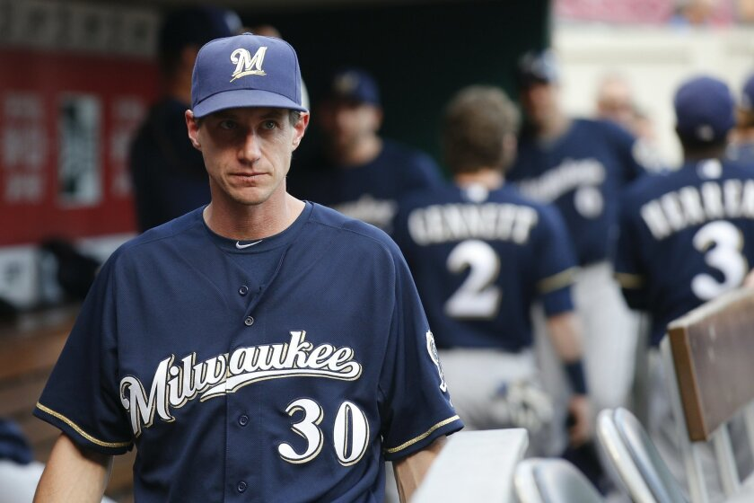 FILE - In this Sept. 5, 2015, file photo, Milwaukee Brewers manager Craig Counsell walks through the dugout before the second game of a baseball doubleheader against the Cincinnati Reds in Cincinnati. The Brewers are rebuilding, and Counsell will start to lay down the foundation for the future in s