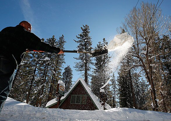 Tony Montenegro shovels snow from the entrance to the Grey Squirrel Resort on Highway 18 near Big Bear Lake as the area recovers from a week of storms.