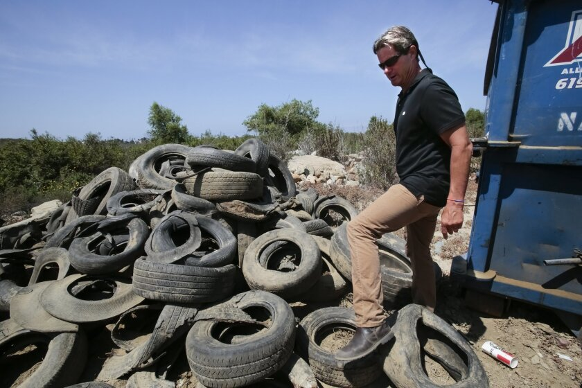 Serge Dedina (cq), mayor from Imperial Beach walks past a large stack of tire debris collected from the Tijuana River Valley. The debris is result of what gets washed into the river from south of the border during a rain storm and eventually makes it's way north of the border.