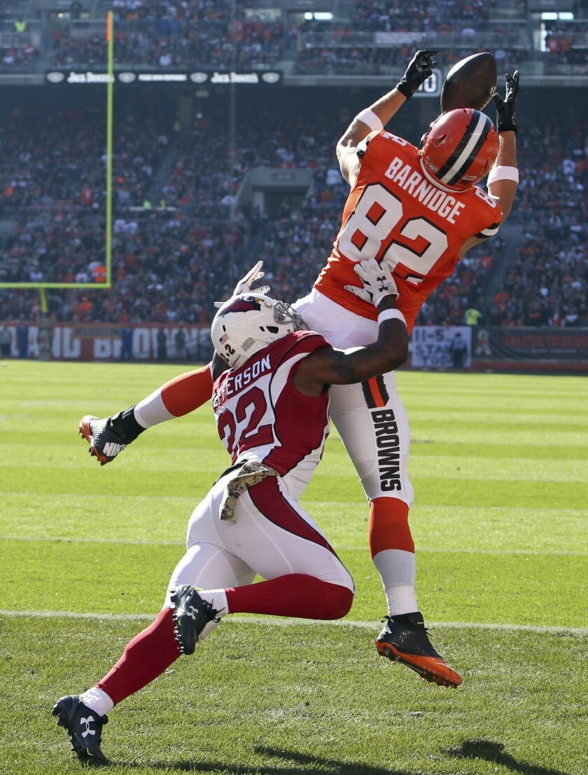 Cleveland Browns tight end Gary Barnidge (82) catches a 3-yard touchdown pass under pressure from Arizona Cardinals strong safety Tony Jefferson (22) in the first half of an NFL football game, Sunday, Nov. 1, 2015, in Cleveland. (AP Photo/Ron Schwane)