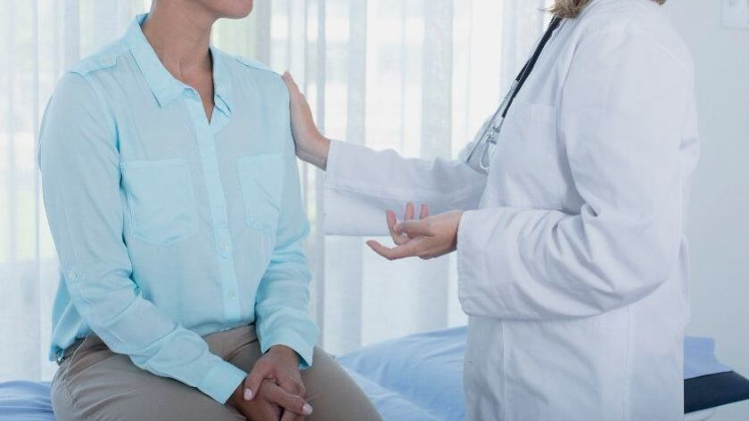 A patient and her doctor speak during a check-up.