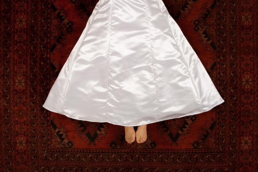 نمای بالا زنی را از کمر به پایین نشان می دهد که روی فرش قرمز براق به سبک ایرانی دراز کشیده است