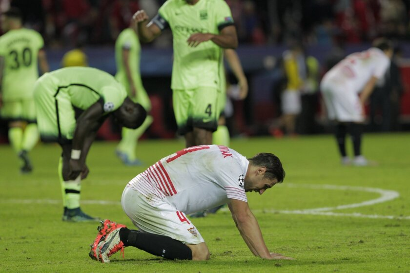 Sevilla's Grzegorz Krychowiak sinks to his knees at the end of the Group D Champions League soccer match between Sevilla and Manchester City at the Ramon Sanchez-Pizjuan stadium in Seville, Spain, Tuesday Nov. 3, 2015. Manchester City won the match 3-1. (AP Photo/Miguel Angel Morenatti)