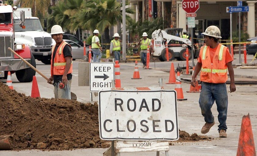 Work to replace aging sewer and water lines continues in downtown La Jolla near the corner of Girard and Kline avenues. Below, Javier Hernandez prepares the corner for concrete as Aerinne Owens walks around it with her Chihuahua. The work is expected to be completed in early July.