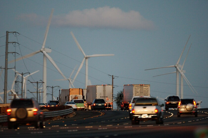 Emissions-producing diesel trucks and cars pass non-polluting windmills along the 10 freeway near Banning, California.