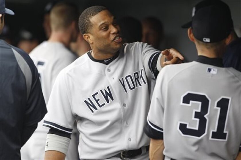 New York Yankees second baseman Robinson Cano, left, jokes with outfielder Ichiro Suzuki before a baseball game against the Colorado Rockies in Denver, Thursday, May 9, 2013. (AP Photo/David Zalubowski)