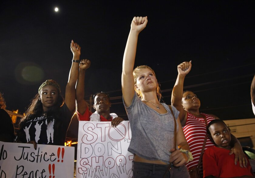 Ella Carr, center, of Austin, Texas, puts her fist up during live music at a night rally in honor of Alton Sterling, outside the Triple S Food mart in Baton Rouge, La., Monday, July 11, 2016. Sterling was shot and killed last Tuesday by Baton Rouge police while selling CD's outside the convenience
