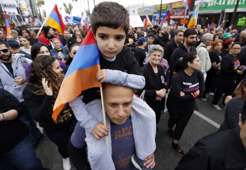 A boy gets a lift from his father during an April 2015 march in L.A. to remember the Armenian genocide.