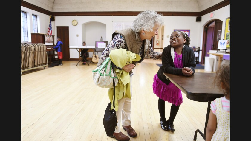 Maua Shukrani, 8, is greeted by church member Charlotte Orr at Holy Spirit Church in Missoula, Monta