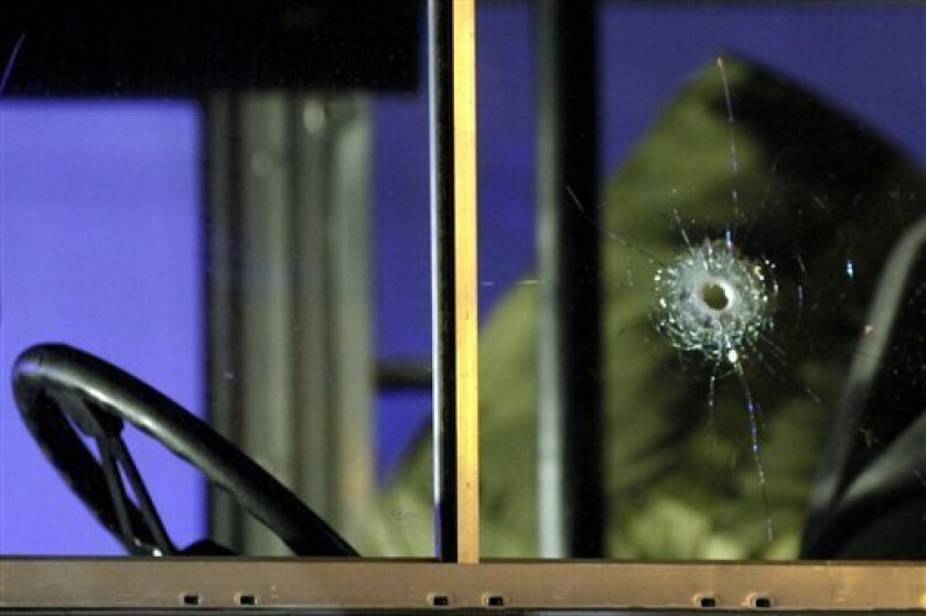 FILE - In this March 2, 2011 file photo a bullet hole is pictured in the window of a bus outside the Frankfurt airport. German federal prosecutors say they have filed murder charges against a 21-year-old Kosovo Albanian in the slaying of two U.S. airmen outside the Frankfurt airport. Prosecutors said in a statement Thursday, July 7, 2011 that Arid Uka was charged with two counts of murder and three counts of attempted murder in connection with the March 2 attack. (AP Photo/dapd, Mario Vedder)