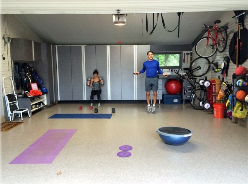 In this photo provided by Tailored Living/Premier Garage, Todd Carter of Tailored Living featuring Premier Garage decided to clean up the a messy garage space to make it more attractive and useful. Carter added wall storage systems and flooring to transform the space into a workout room. (Tailored