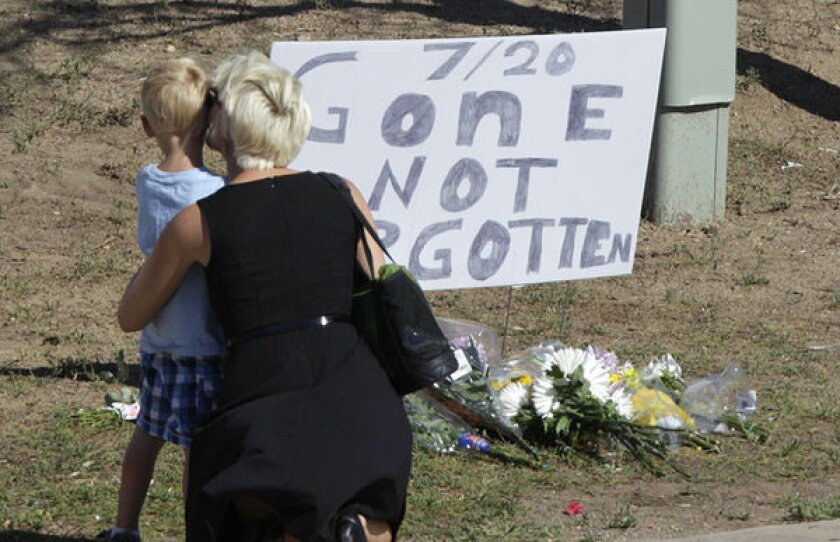 """A woman and a child stand near a sign that reads, """"7/20 Gone Not Forgotten,"""" near the movie theater where a gunman killed at least 12 people and wounded dozens of others in Aurora, Colo."""