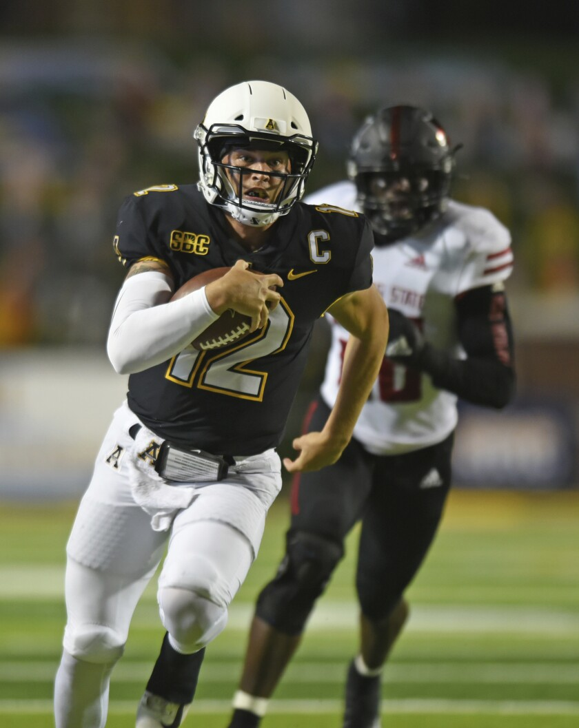Appalachian State quarterback Zac Thomas, front, scrambles for a first down ahead of Arkansas State linebacker Jeffmario Brown in the first half of an NCAA college football game, Thursday, Oct. 22, 2020, at Kidd Brewer Stadium in Boone, N.C. (Walt Unks/Winston-Salem Journal via AP)