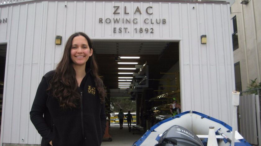 Allison Komiyama, athletic chair for ZLAC, poses with a rubber dinghy in front of the ZLAC boathouse