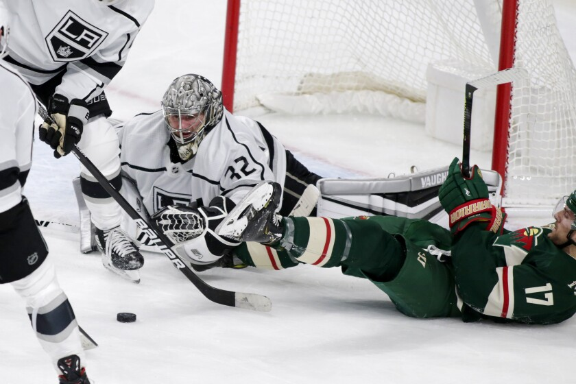 Kings goalie Jonathan Quick stops a shot in front of Minnesota Wild forward Marcus Foligno.