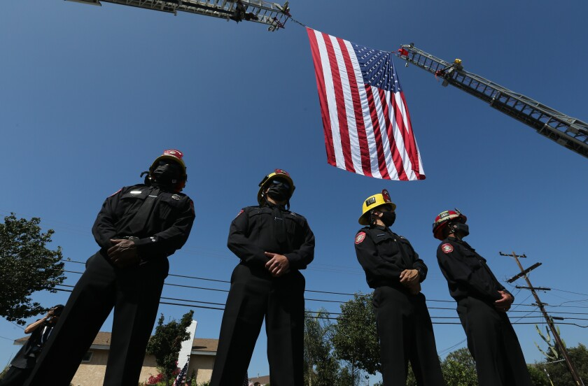Anaheim Fire Department firefighters line up under a flag arch as motorcade carrying Charles Morton's body passes Tuesday.