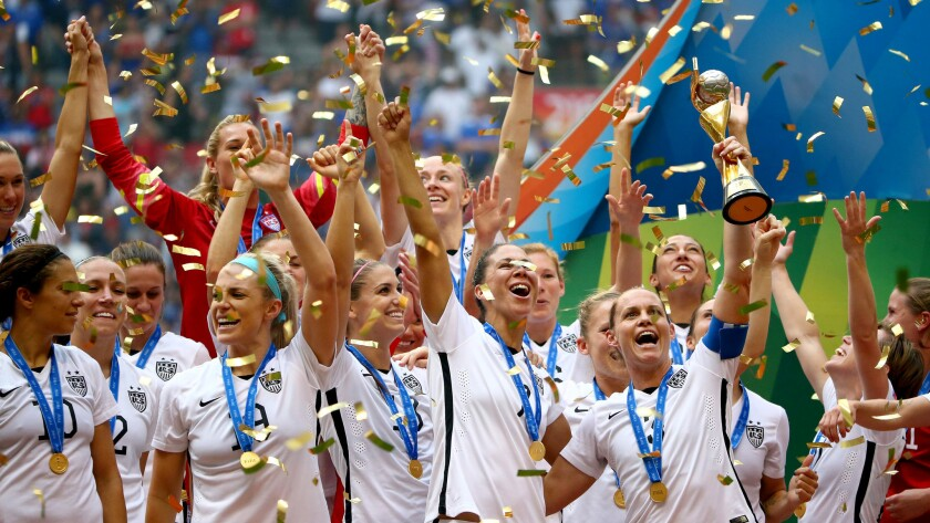 Christie Rampone, the oldest player to appear in a World Cup final at 40, holds aloft the trophy as U.S. players celebrate during the awards ceremony on Sunday at BC Place in Vancouver, Canada.