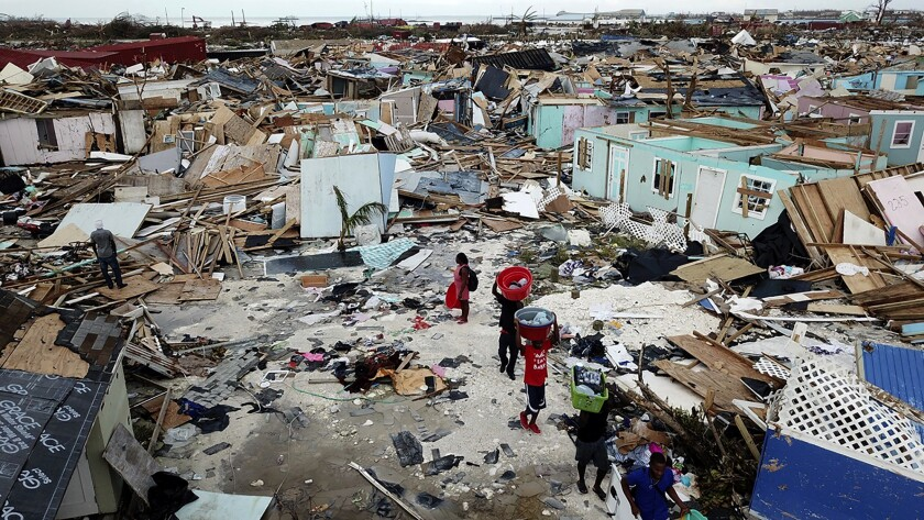 People search for salvageable items as they make their way through an area destroyed by Hurricane Dorian at Marsh Harbour in Great Abaco Island, Bahamas on Thursday, Sept. 5, 2019. (Al Diaz/Miami Herald via AP)