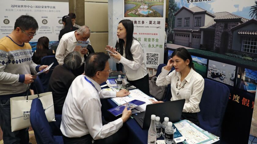Chinese visitors seek information about the U.S. government's EB-5 visa program at an Invest in America Summit in Beijing on May 7, 2017.