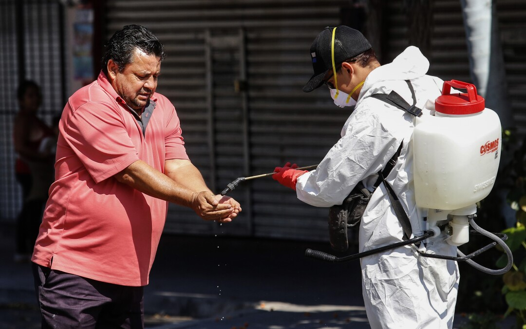 MEXICO: A worker sprays disinfectant on a man's hands in Guadalajara.