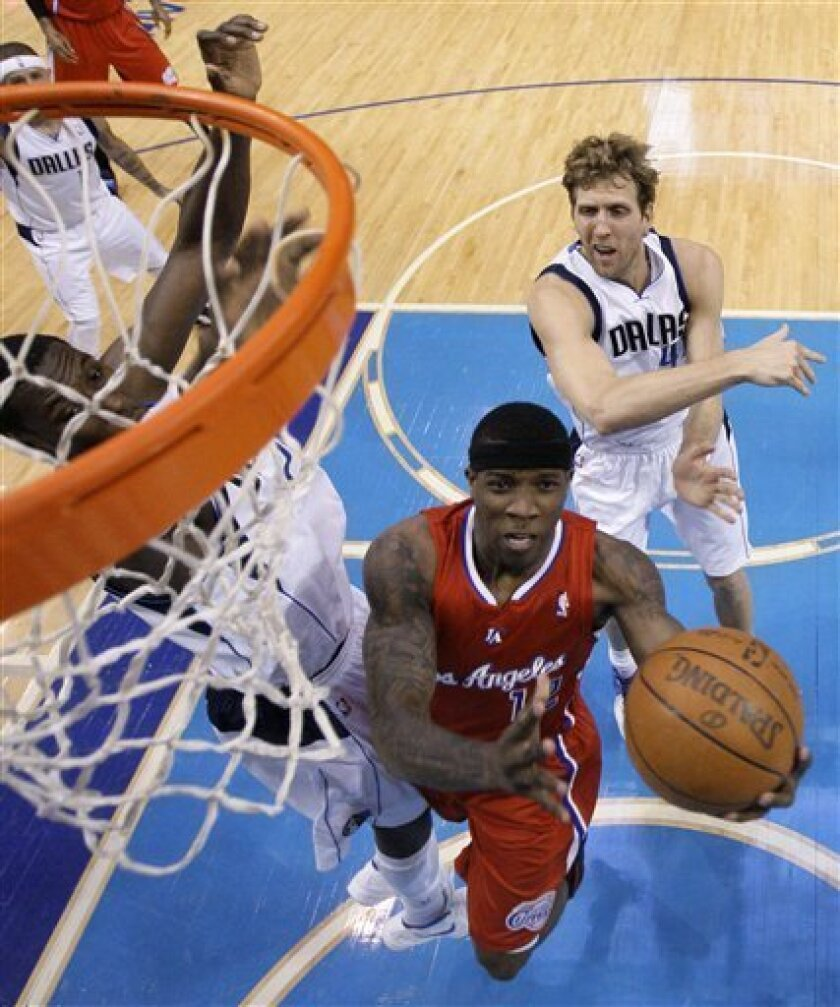 Los Angeles Clippers' Eric Bledsoe, bottom right, goes up for a shot as Dallas Mavericks' Ian Mahinmi, left, and Dirk Nowitzki, right rear, defend in the first half of an NBA basketball game Monday, April 2, 2012, in Dallas. (AP Photo/Tony Gutierrez)
